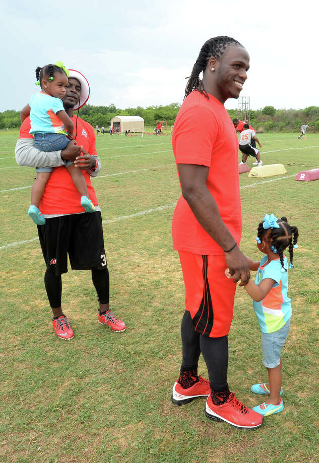 Danny Gorrer, left, holds Makenzie Charles, 2, while Jamaal Charles, 2, holds hands with Makaila Charles, 3, during the famed football player's sports camp at Memorial High School on Friday. Photo taken Friday, June 13, 2014 Guiseppe Barranco/@spotnewsshooter Photo: Guiseppe Barranco, Photo Editor