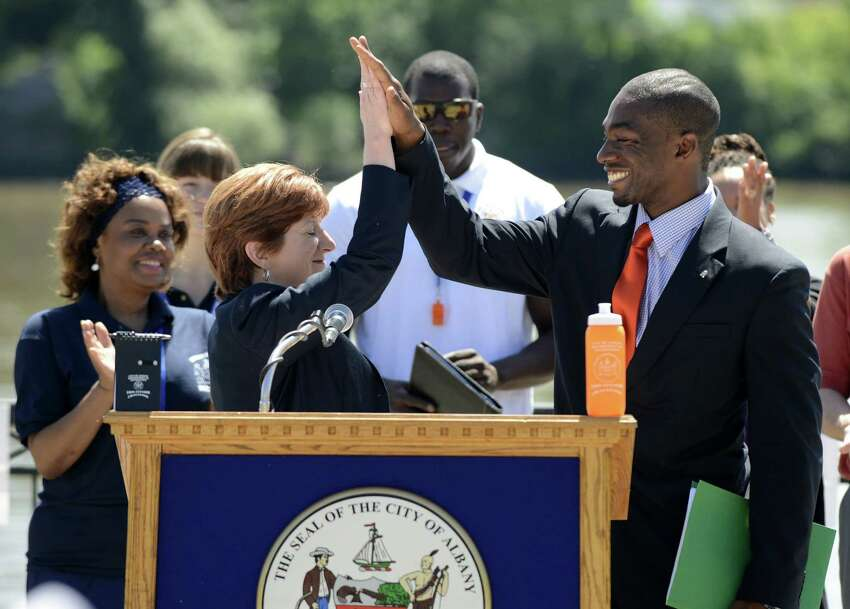 Albany Mayor Kathy Sheehan, left, and recreation commissioner Jonathan Jones, right, give a celebratory high five after blowing whistles to start a 67-day fitness initiative called the 1609 Fitness Challenge Monday morning, June 16, 2014, at Jennings Landing in Albany, N.Y. The challenge is designed to encourage Albany residents to partake in 30 minutes of daily exercise from June 16 through Aug. 22. Points are awarded for exercise, with prizes offered to the most active participants. (Will Waldron/Times Union)