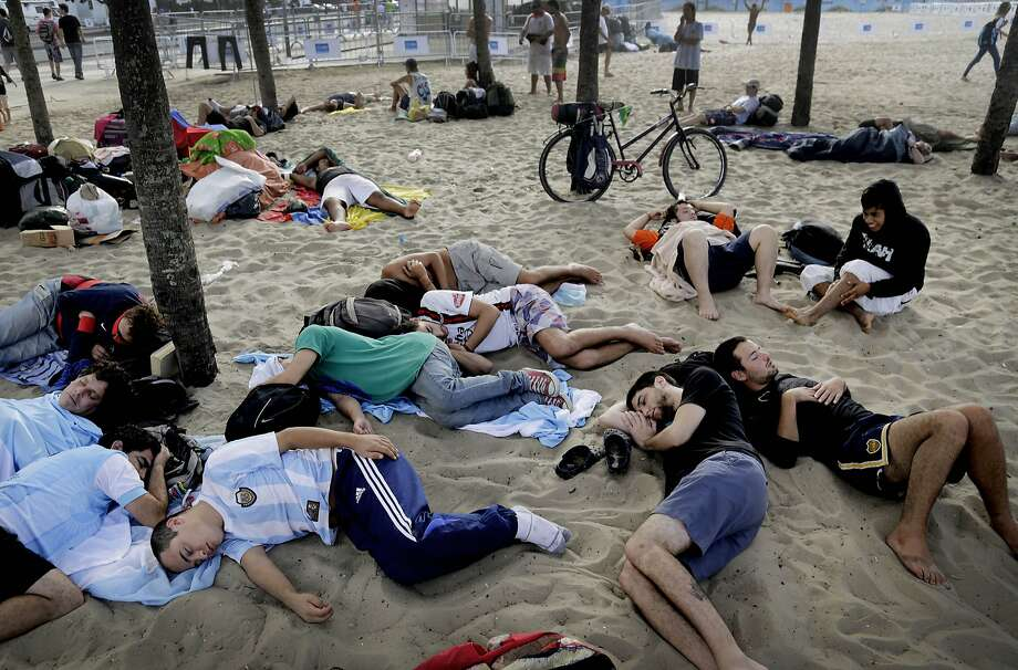 The morning after: In Rio, young soccer fans sleep off a night of partying in a Copacabana beach fan zone  where matches are broadcast live. Photo: Wong Maye-E, Associated Press