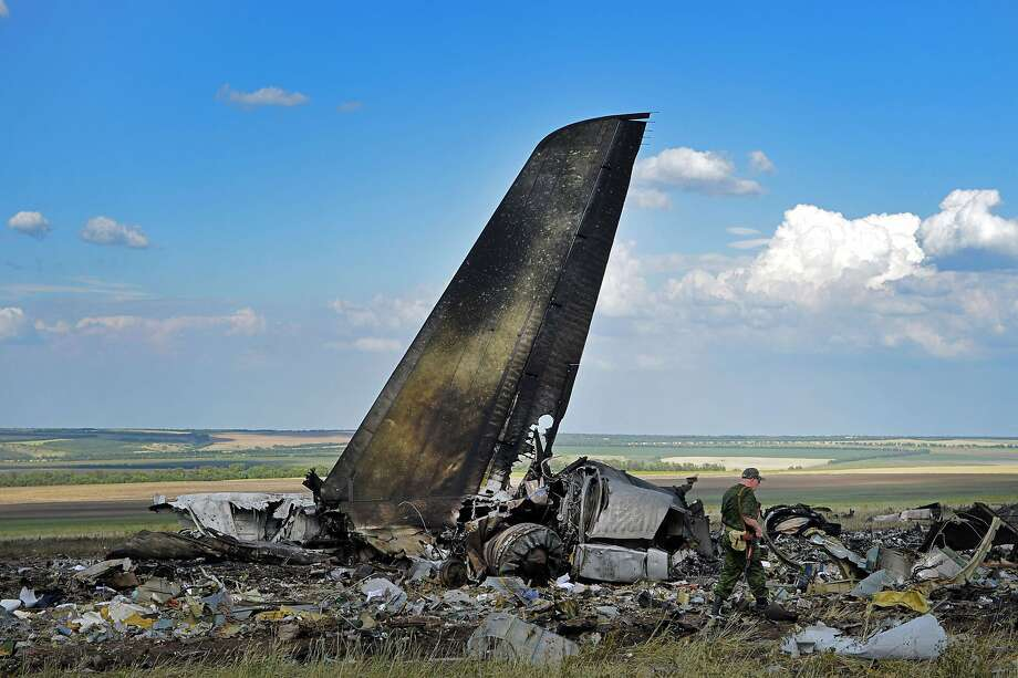 "Deadliest incident yet: Pro-Russian militants look through the debris of an IL-76 Ukrainian military transporter that separatists shot down on the outskirts of Lugansk, killing 40 troops and nine crew members. Ukraine's new President Petro Poroshenko vowed to deliver an ""adequate response"" to the attack. Photo: Daniel Mihailescu , AFP/Getty Images"