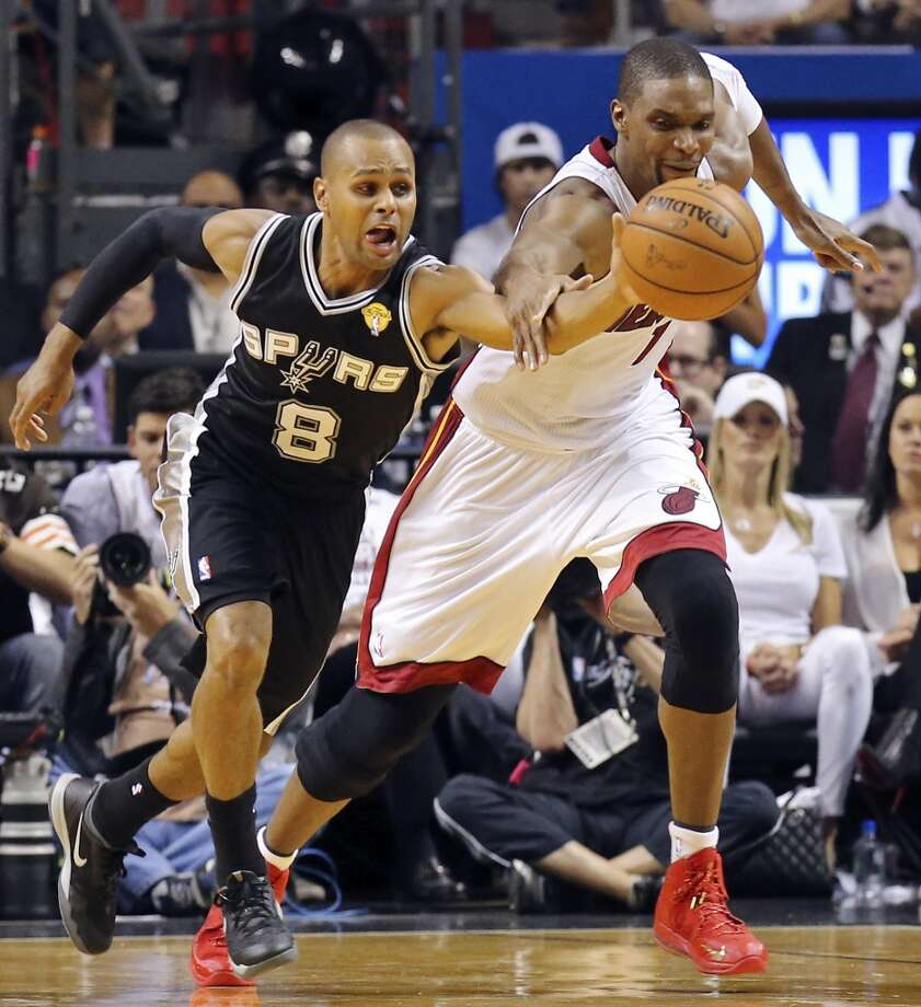 San Antonio Spurs' Patty Mills and Miami Heat's Chris Bosh chase after a loose ball in Game 3 of the NBA Finals Tuesday June 10, 2014 at American Airlines Arena in Miami, Fla. Photo: Edward A. Ornelas, San Antonio Express-News