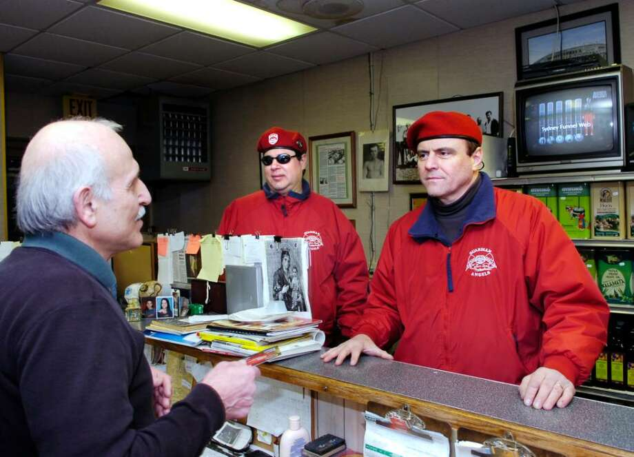 CEO and founder of The Guardian Angels, right, Curtis Sliwa, speaks with Phil Kydes, left, who is the owner of Steve's Market on Main Street in Norwalk.  Also in photo is Guardian Angel, Salvatore Galaz of Norwalk, center.   The Guardian Angels, a non-profit volunteer crime patrol organization composed of citizens, have begun patrols in Norwalk, Monday, Feb. 15th, 2010. Photo: Bob Luckey / Stamford Advocate