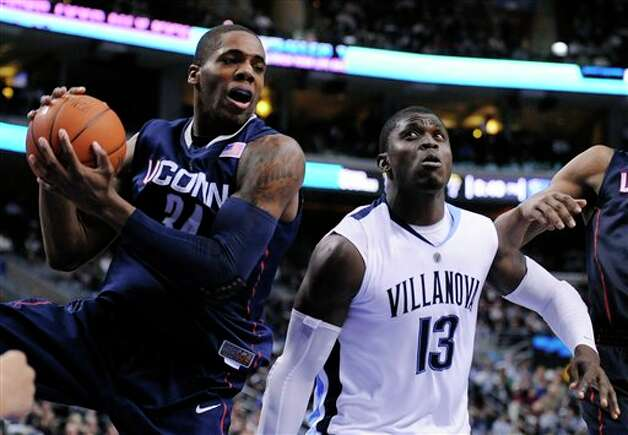 Connecticut center Alex Oriakhi (34) pulls in a rebound next to Villanova center Mouphtaou Yarou, of Benin, in the second half of an NCAA college basketball game Monday, Feb. 15, 2010, in Philadelphia. Connecticut won 84-75. (AP Photo/Michael Perez) /