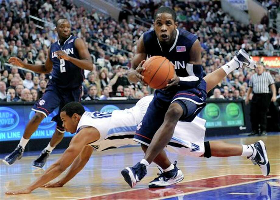 Connecticut guard Jerome Dyson drives past a diving Villanova guard Corey Fisher in the first half of a NCAA college basketball game Monday, Feb. 15, 2010, in Philadelphia. (AP Photo/Michael Perez) /