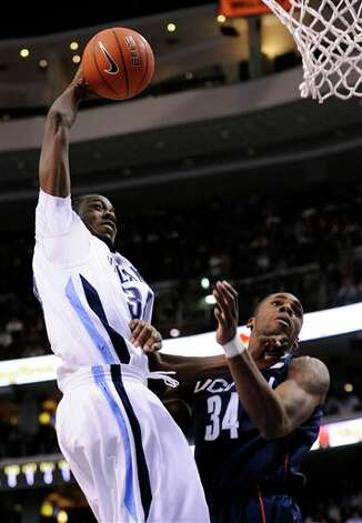Villanova forward Isaiah Armwood dunks over Connecticut forward Alex Oriakhi (34) in the first half of a NCAA college basketball game Monday, Feb. 15, 2010, in Philadelphia. (AP Photo/Michael Perez) /