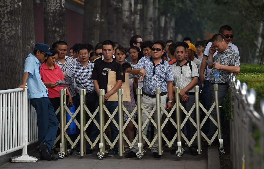 Visitors wait behind a barrier to go through a security check to enter Tiananmen Square, the site of a suicide attack which left five people dead last October, in Beijing on June 16, 2014. Three people were sentenced to death on June 16 over the suicide car crash in Beijing's symbolic heart Tiananmen Square, state-run media said, in China's latest move against militants from restive, mainly Muslim Xinjiang.  AFP PHOTO / GREG BAKERGREG BAKER/AFP/Getty Images Photo: Greg Baker, AFP/Getty Images