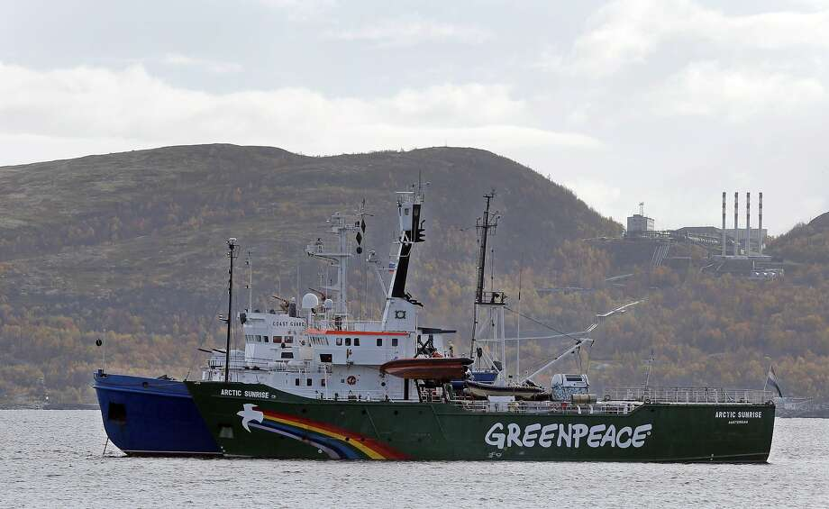 FILE - In this Tuesday, Sept. 24, 2013 file photo, Greenpeace ship 'Arctic Sunrise'  is escorted by a Russian coast guard boat, in Kola Bay at the military base Severomorsk on the Kola peninsula in Russia, at dawn. Greenpeace has suffered a 3.8 million-euro ($5.2 million) loss on an ill-timed bet in the currency market by a well-intentioned ? if reckless ? employee in its financial unit. The environmental group, which is based in Amsterdam, said Monday, June 16, 2014,  the employee ? who had bet the euro would not strengthen against other currencies in 2013, when it did ? had acted beyond the limits of his authority. (AP Photo/Efrem Lukatsky, File) Photo: Efrem Lukatsky, Associated Press