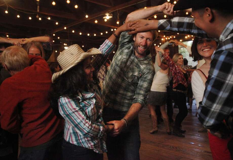 "From left, Birza Santiago, 26, Brian Boyce, 30, Stacey Garcia, 31, and Jesus Jocobo, 37, laugh as they do a group dance move together during the monthly barn dance May 17, 2014 at Pie Ranch in Pescadero, Calif. Every month, the educational farm holds a work day and welcomes people to volunteer at the farm. Afterwards, people gather for a potluck and then an evening of traditional barn dancing with a caller and a live band. Margaret More has been attending the dance for eight years, she says she enjoys the intergenerational aspect and added, ""it feels like [we've] stepped back 150 years in civilization."" Photo: Leah Millis, The Chronicle"