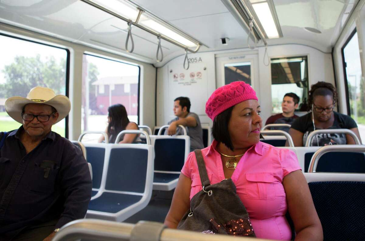 Anna Lopez, center, along with other passengers, ride the North line of the METRO rail Monday, June 16, 2014, in Houston.