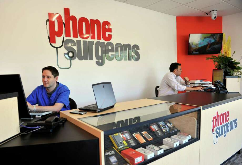 Mike Jacobs, 37, left, of North Salem, N.Y., a co-owner of Phone Surgeons, and Jonathan De Meo, 21, of Brewster, N.Y., man the front desk at Phone Surgeon on Federal Road in Danbury, Conn., Monday, June 16, 2014. Photo: Carol Kaliff / The News-Times