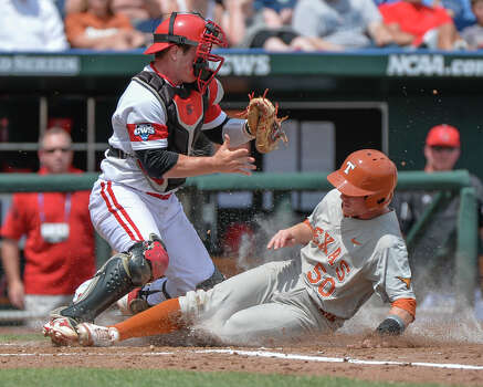 Texas' Zane Gurwitz scores at home plate against Louisville catcher Kyle Gibson, left, in the third inning of an NCAA baseball College World Series elimination game in Omaha, Neb., Monday, June 16, 2014. (AP Photo/Ted Kirk) Photo: Ted Kirk, Associated Press / FR34398 AP