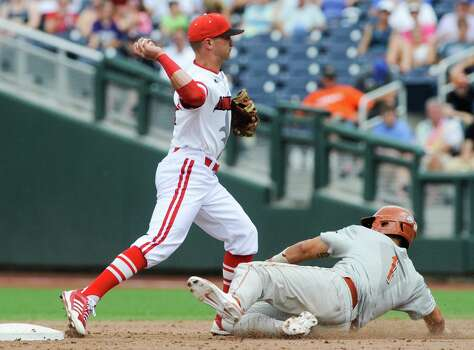 Louisville second baseman Zach Lucas (11) throws to first after forcing out Texas' Tres Barrera in the fifth inning of an NCAA baseball College World Series elimination game in Omaha, Neb., Monday, June 16, 2014. (AP Photo/Eric Francis) Photo: Eric Francis, Associated Press / FR9944 AP