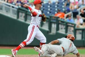Louisville second baseman Zach Lucas (11) throws to first after forcing out Texas' Tres Barrera in the fifth inning of an NCAA baseball College World Series elimination game in Omaha, Neb., Monday, June 16, 2014. (AP Photo/Eric Francis)