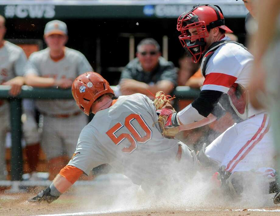 Texas'  Zane Gurwitz (50) scores at home plate against Louisville catcher Kyle Gibson, right, in the third inning of an NCAA baseball College World Series elimination game in Omaha, Neb., Monday, June 16, 2014. (AP Photo/Eric Francis) Photo: Eric Francis, Associated Press / FR9944 AP