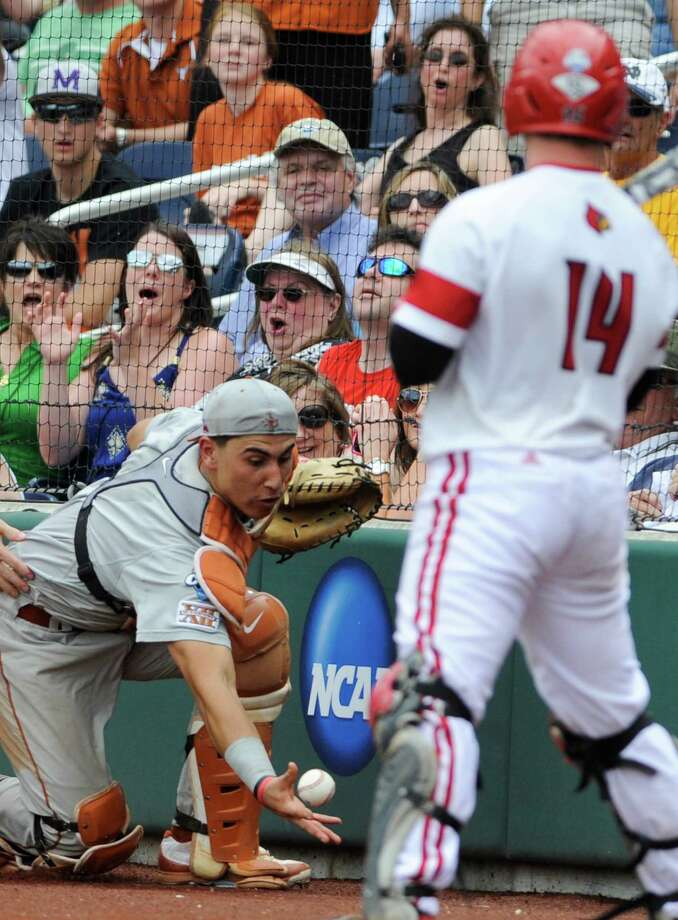 Texas catcher Tres Barrera, left, reaches for but does not catch a foul ball hit by Louisville's Kyle Gibson (14) in the fifth inning of an NCAA baseball College World Series elimination game in Omaha, Neb., Monday, June 16, 2014. (AP Photo/Eric Francis) Photo: Eric Francis, Associated Press / FR9944 AP