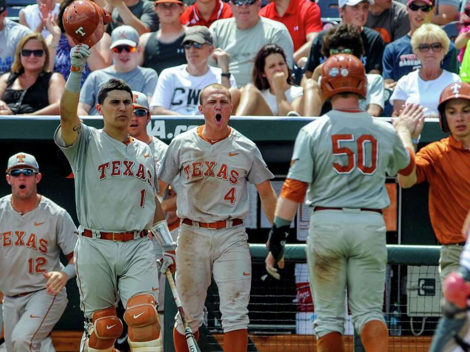 Texas' Zane Gurwitz (50) is greeted at the dugout by teammates Tres Barrera (1), Collin Shaw (4) and Jacob Felts (12) after he scored a run on a sacrifice fly by Ben Johnson in the third inning of an NCAA baseball College World Series elimination game in Omaha, Neb., Monday, June 16, 2014. (AP Photo/Eric Francis) Photo: Eric Francis, Associated Press / FR9944 AP