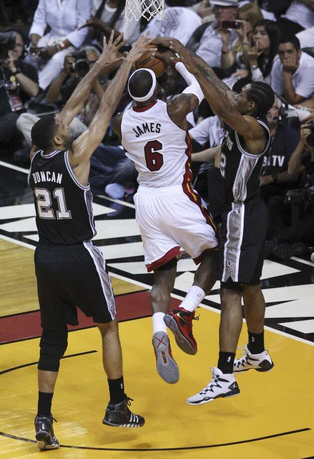 Miami Heat's LeBron James (06) gets defended by Spurs' Tim Duncan (21) and Kawhi Leonard (02) in the first half of Game 3 of the 2014 NBA Finals at the American Airlines Arena in Miami on Tuesday, June 10, 2014. (Kin Man Hui/San Antonio Express-News) Photo: Kin Man Hui, San Antonio Express-News
