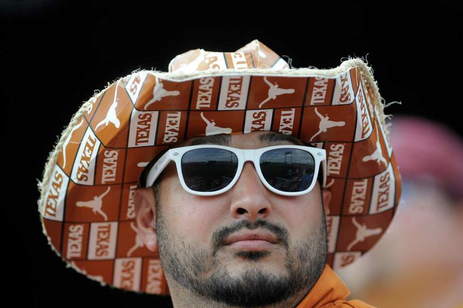 Texas fan Luciano Rivera follows the action in an NCAA baseball College World Series elimination game between Texas and Louisville in Omaha, Neb., Monday, June 16, 2014. (AP Photo/Eric Francis) Photo: Eric Francis, Associated Press / FR9944 AP