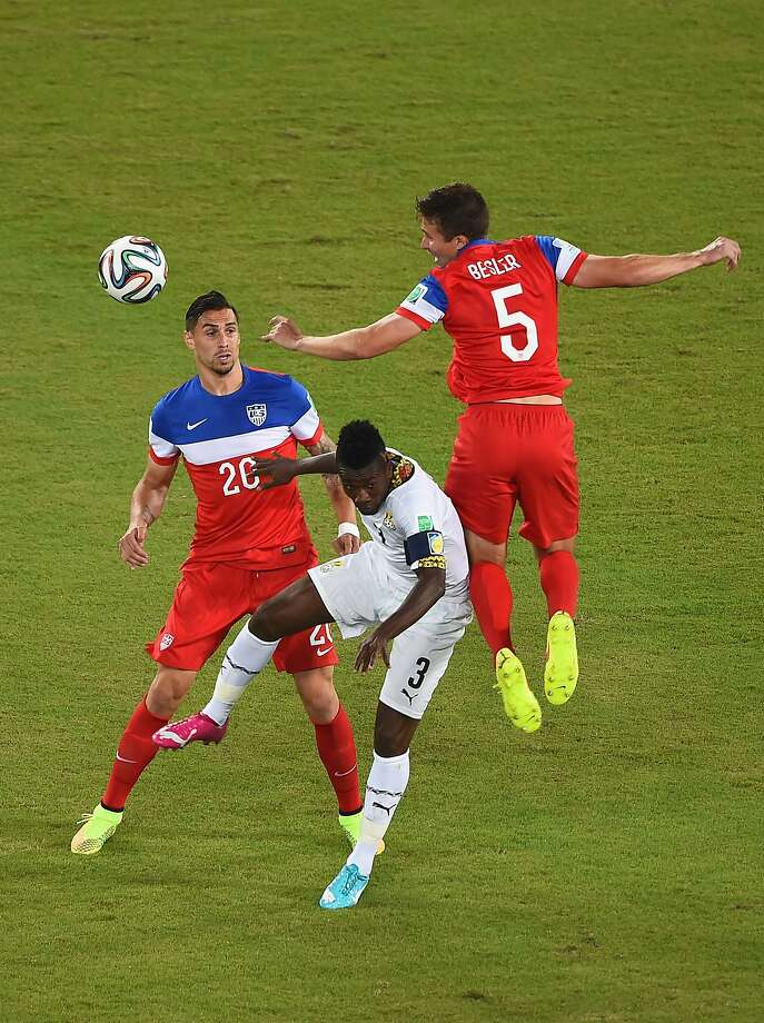 Matt Besler of the United States and Asamoah Gyan of Ghana go up for a header as Geoff Cameron of the United States looks on during the 2014 FIFA World Cup Brazil Group G match between Ghana and the United States at Estadio das Dunas on June 16, 2014 in Natal, Brazil.  Photo: Laurence Griffiths, Getty Images