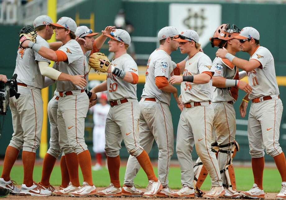 Texas players congratulate each other after beating Louisville 4-1in an NCAA baseball College World Series elimination game in Omaha, Neb., Monday, June 16, 2014. (AP Photo/Ted Kirk) Photo: Ted Kirk, Associated Press / FR34398 AP