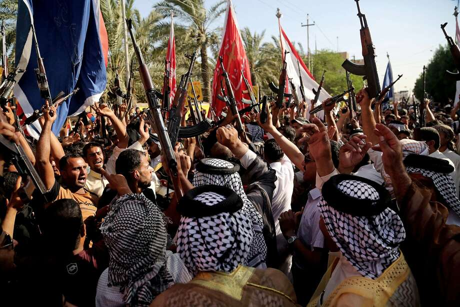 Shiite tribal fighters raise their weapons and chant slogans against the al-Qaida-inspired Islamic State of Iraq and the Levant (ISIL) in Basra, Iraq's second-largest city, 340 miles (550 kilometers) southeast of Baghdad, Iraq, Monday, June 16, 2014. Sunni militants captured a key northern Iraqi town along the highway to Syria early on Monday, compounding the woes of Iraq's Shiite-led government a week after it lost a vast swath of territory to the insurgents in the country's north. (AP Photo/Nabil Al-Jurani) Photo: Nabil Al-Jurani, Associated Press