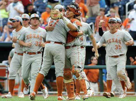 Texas catcher Tres Barrera (1) hugs Texas pitcher Travis Duke (27) after the last out against Louisville in an NCAA baseball College World Series elimination game in Omaha, Neb., Monday, June 16, 2014. Texas won 4-1. (AP Photo/Eric Francis) Photo: Eric Francis, Associated Press / FR9944 AP