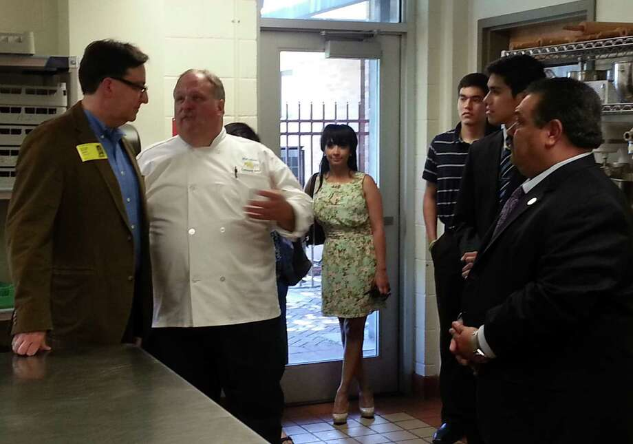 Rep. Pete Gallego, left, chats with Chef Johnny Stewart after a tour as Principal Aracelie Bunsen, center, and HISD Superintendent Rey Madrigal, right, and students look on. Photo: Jeremy Gerlach / Southside Reporter