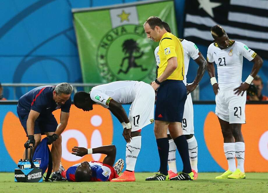 An injured Jozy Altidore of the United States lies on the field as Mohammed Rabiu of Ghana  stands over during the 2014 FIFA World Cup Brazil Group G match between Ghana and the United States at Estadio das Dunas on June 16, 2014 in Natal, Brazil. Photo: Kevin C. Cox, Getty Images