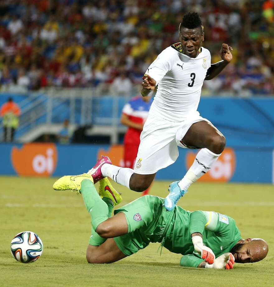 Ghana's Asamoah Gyan (3) leaps over United States' goalkeeper Tim Howard during the group G World Cup soccer match between Ghana and the United States at the Arena das Dunas in Natal, Brazil, Monday, June 16, 2014.  Photo: Julio Cortez, Associated Press