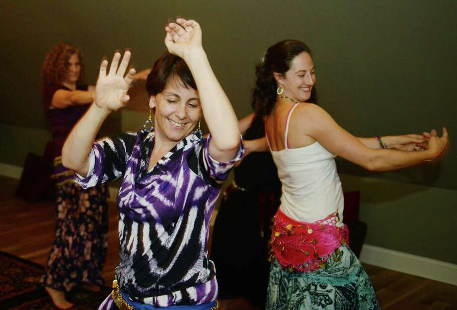 Laura Volpintesta, center, of Bethel, and Kalena Trow, right, of Naugatuck, dance with others during the Sacred Bellydance class at the SOUND Center for Music & Arts in Newtown, Conn. Friday, June 13, 2014.  Sacred bellydance uses gentle circular movements while implementing coin belts and silk scarves to inspirational, tribal music.  The dance is designed to help women explore the mystery and secrets within themselves while strengthening their bodies in a relaxed and peaceful atmosphere. Photo: Tyler Sizemore / The News-Times