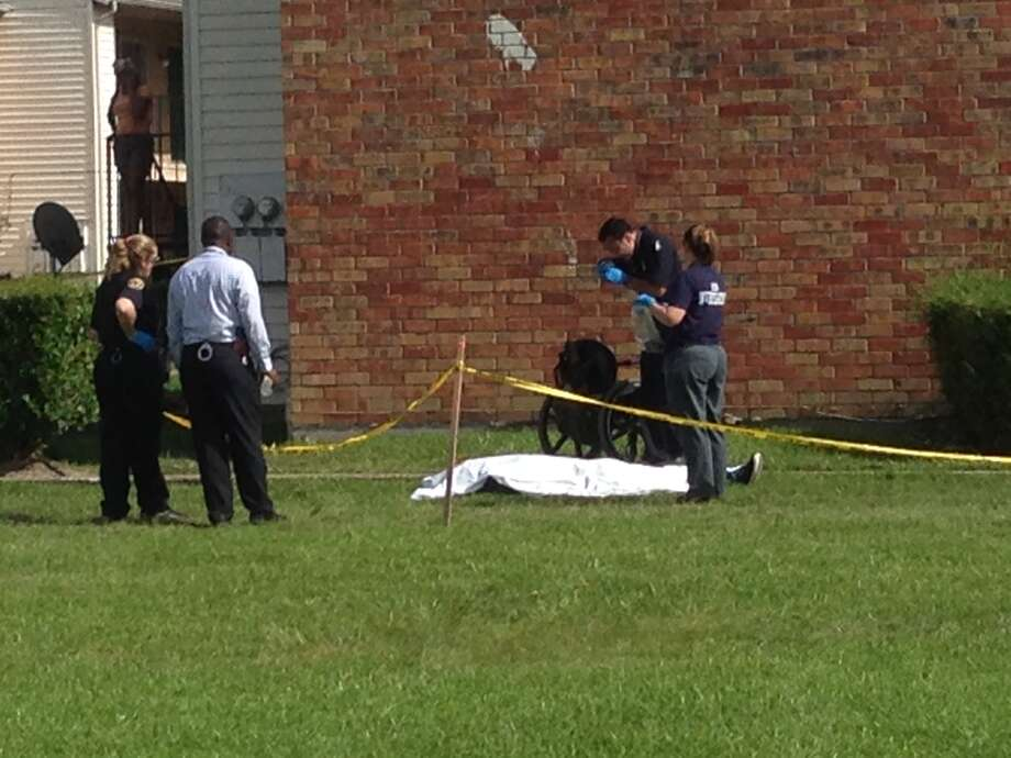 Police are questioning possible witnesses to the fatal shooting Monday of a man in a wheelchair at northeast Houston apartment complex. Police stretched crime scene tape around a grassy area at the complex where the dead man was covered with a sheet.(Photo by Mike Glenn / Houston Chronicle)