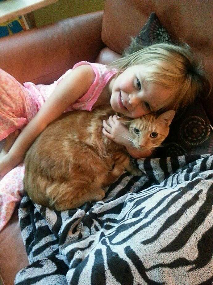 Laura Marquez and Dan Christian's daughter Tessa with their orange tabby Woody Guthrie. Photo: Dan Christian