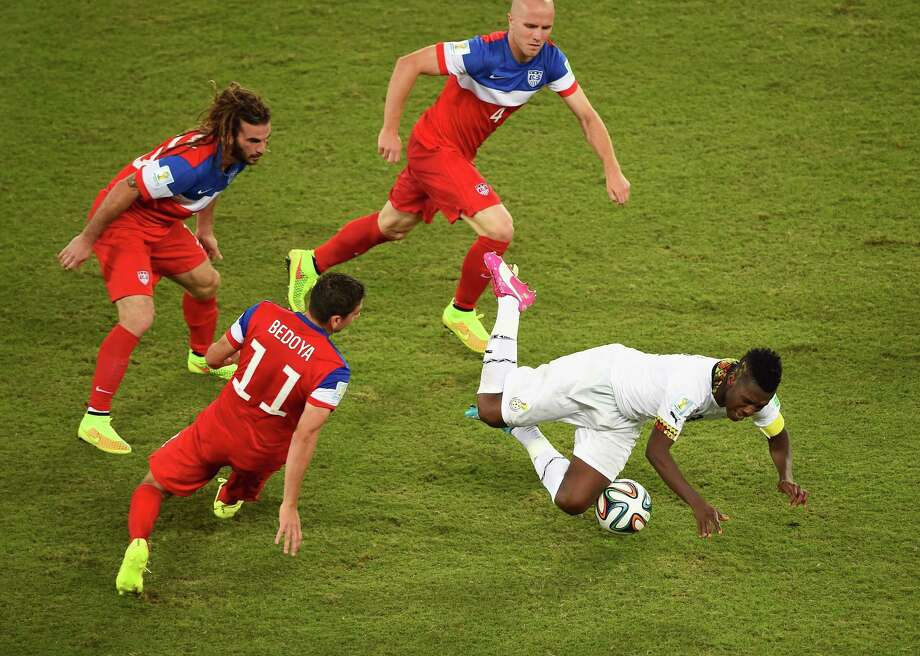 NATAL, BRAZIL - JUNE 16: Asamoah Gyan of Ghana falls after a challenge by Alejandro Bedoya of the United States as teammates Kyle Beckerman (L) and Michael Bradley (2nd R) run on during the 2014 FIFA World Cup Brazil Group G match between Ghana and the United States at Estadio das Dunas on June 16, 2014 in Natal, Brazil. Photo: Laurence Griffiths, Getty Images / 2014 Getty Images