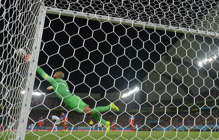US goalkeeper Tim Howard dives for the ball during a Group G football match between Ghana and US at the Dunas Arena in Natal during the 2014 FIFA World Cup on June 16, 2014.  AFP PHOTO / CARL DE SOUZA Photo: CARL DE SOUZA, AFP/Getty Images / AFP