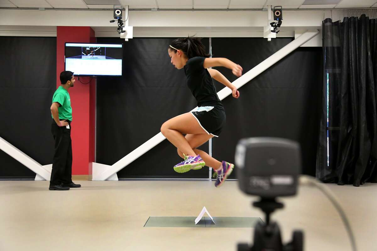 Lauren Wong, 16, of Oakland performs a jumping exercise while physical therapist Neeraj Baheti watches data of her condition on a monitor in the motion analysis and sports performance lab at the Children's Hospital Oakland Walnut Creek campus on Monday, June 2, 2014 in Walnut Creek, Calif. Wong tore her ACL during a soccer game in October, which required surgery in November.