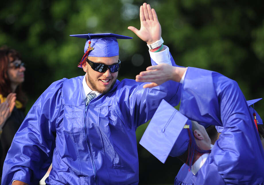 Colin Lydiksen, left, high fives a fellow graduate after receiving his diploma during graduation at Joseph A. Foran High School in Milford, Conn. on Monday, June 16, 2014. Photo: Brian A. Pounds / Connecticut Post