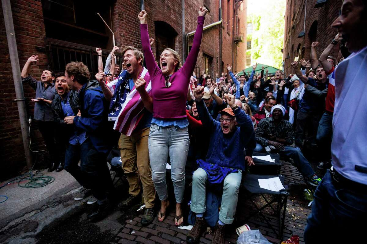 Fans react to the U.S. versus Ghana World Cup soccer match at a viewing party consisting of a TV set up in the back of a U-Haul truck Monday, June 16, 2014, in a Pioneer Square alley in Seattle, Wash. USA beat Ghana 2-1 in stoppage time.