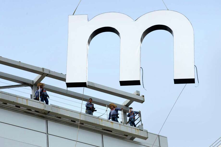 Workers install a portion of  the new sign on the exterior of the former Reliant Stadium, that is now NRG Stadium, on June 16, 2014. Photo: Brett Coomer, Houston Chronicle / © 2014  Houston Chronicle