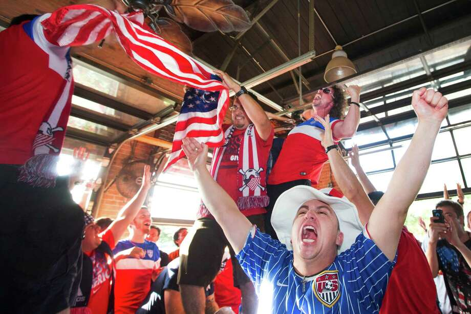 United States soccer fan Flavio Melucci, lower right, celebrates the Americans' 2-1 World Cup win over Ghana  during a watch party at Lucky's Pub Monday, June 16, 2014, in Houston. Photo: Brett Coomer, Houston Chronicle / © 2014 Houston Chronicle