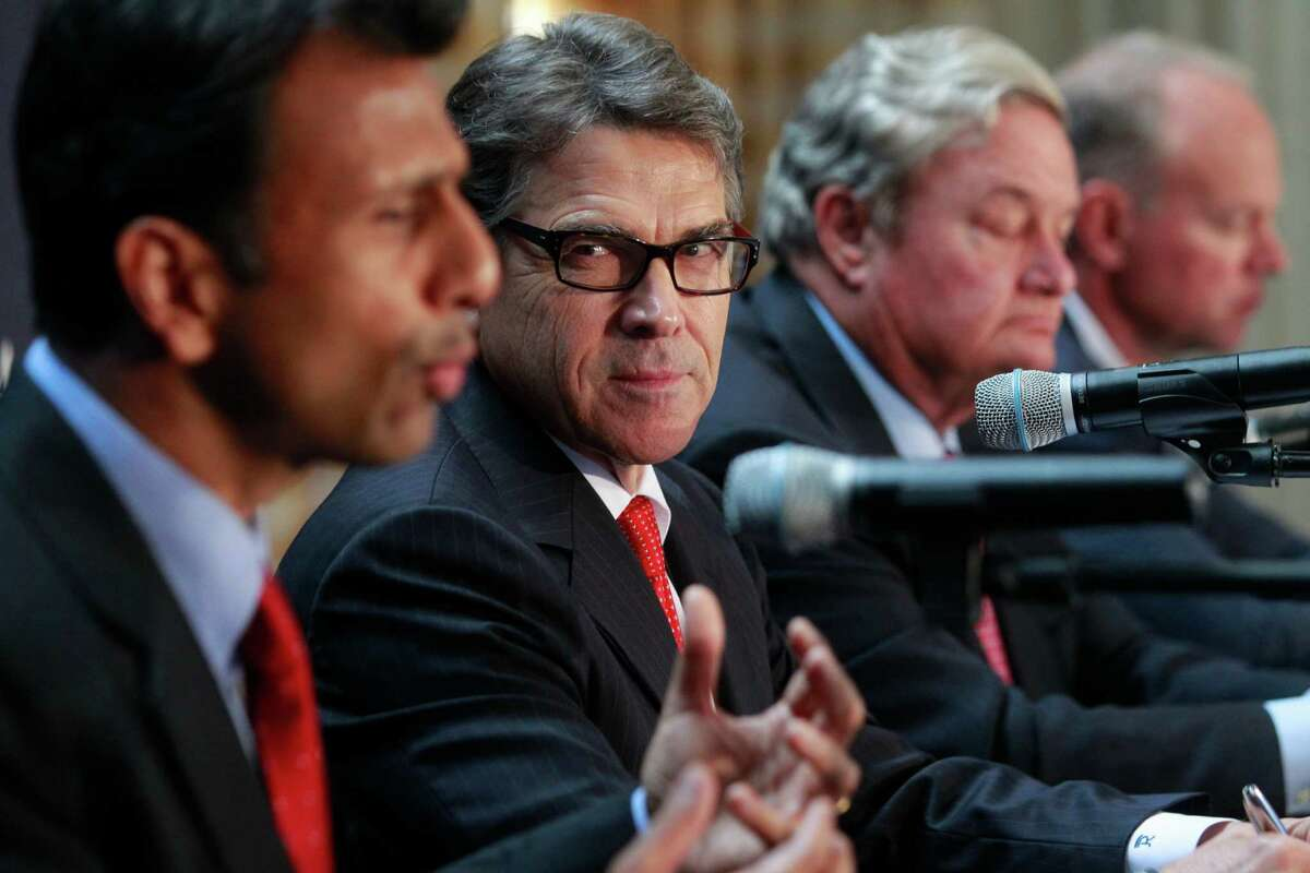 Louisiana Gov. Bobby Jindal, left, meets with Texas Gov. Rick Perry and others June 16, 2014, at the Republican Governors Association media conference held at the Petroleum Club in Houston. Jindal toured the Mexico border area Monday. ( Melissa Phillip / Houston Chronicle )
