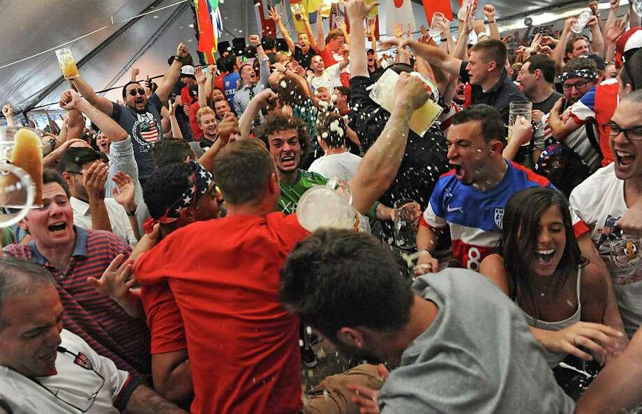 People celebrate after watching U.S. defeat Ghana in the World Cup at a tent party held by Wolff's Biergarten Monday June 16, 2014 in Albany, N.Y.  (Lori Van Buren / Times Union) Photo: Lori Van Buren / 00027348A
