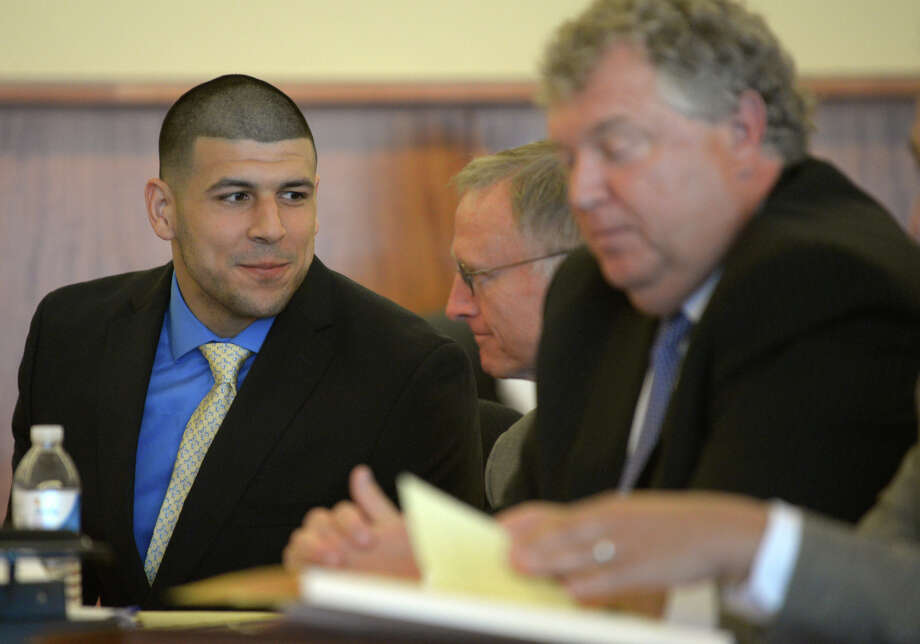 Former  New England Patriots football player Aaron Hernandez, left,  confers with his defense attorney, Charles Rankin during a hearing at the Bristol County Superior Court House in Fall River, Mass., Monday  June 16, 2014. Hernandez's attorneys on Monday sought to have a murder charge dismissed, saying prosecutors don't have enough evidence to tie the former New England Patriots' star to the murder of a semi-professional football player.(AP Photo/Faith Ninivaggi, Pool) ORG XMIT: NY207 Photo: FAITH NINIVAGGI / Pool EPA