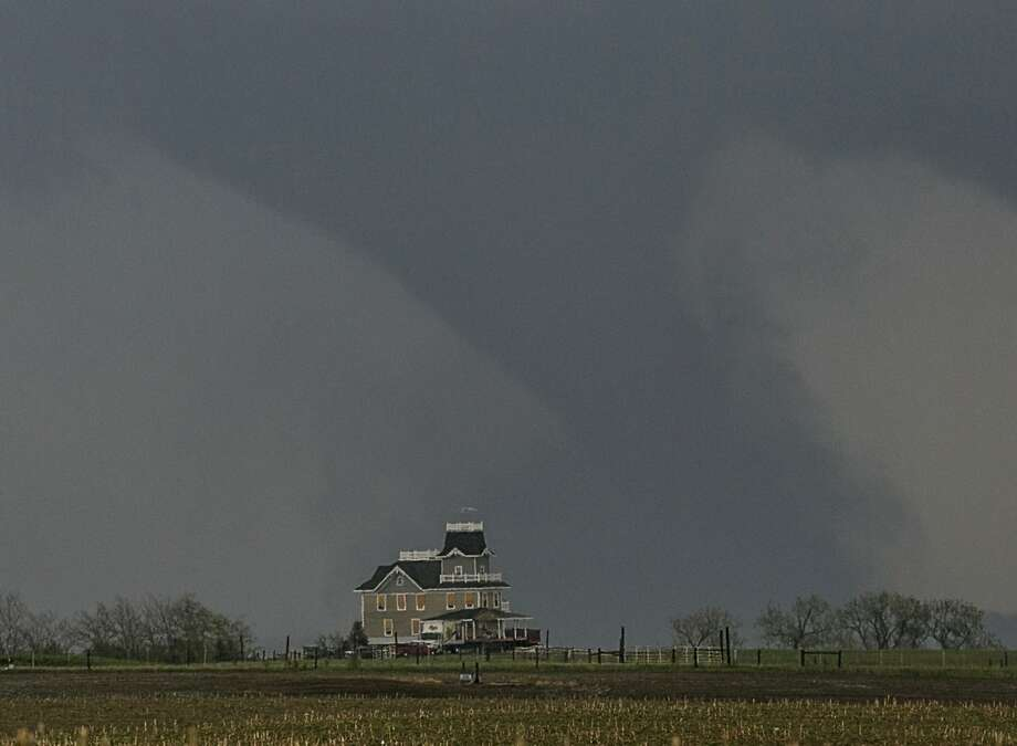 A tornado forms over a house near  Pilger, Neb., Monday, June 16, 2014. At least one person is dead and at least 16 more are in critical condition after two massive tornadoes swept through northeast Nebraska on Monday. (AP Photo/Mark 'Storm' Farnik) Photo: Mark 'Storm' Farnik, Associated Press