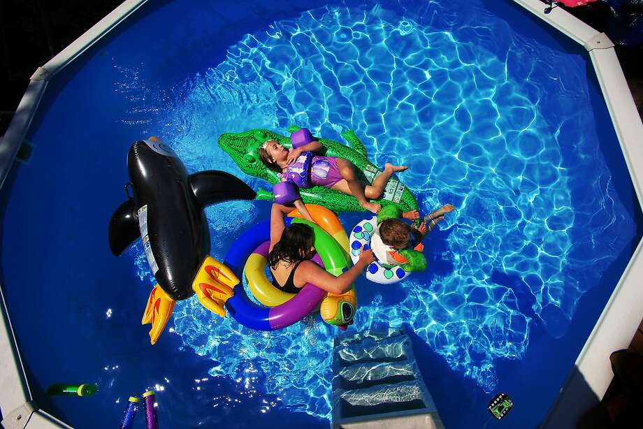 The Domski children, from top: Miley, 6,  Maggie, 11, and Hunter, 3, relax in their backyard pool on Monday, June 16, 2014, in Blakely, Pa.     (AP Photo / The Scranton Times-Tribune, Butch Comegys)  WILKES BARRE TIMES-LEADER OUT; MANDATORY CREDIT Photo: Butch Comegys, Associated Press