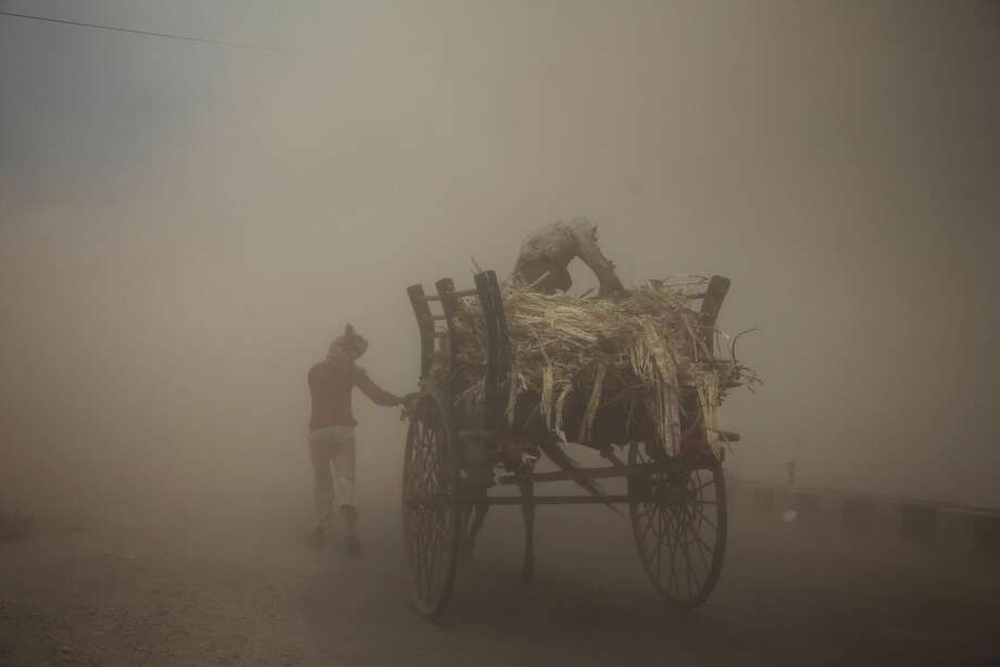 Two men with a horse cart try to make their way during a powerful dust storm in Jammu, India, Monday, June 16, 2014. (AP Photo/Channi Anand) Photo: Channi Anand, Associated Press