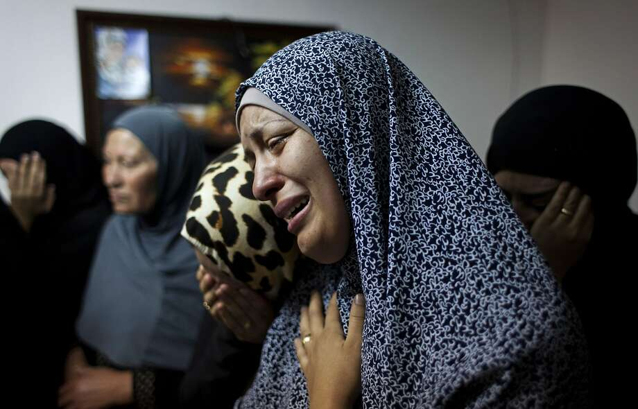 Female relatives of slain Palestinian Ahmad Arafat Sabarin, 20, who was killed by Israeli army fire early Monday during a confrontation between stone throwers and soldiers, cries with a relative at the family house, prior to his funeral procession in the Palestinian refugee camp of Jalazoun, at the outskirts of the West Bank city of Ramallah, Monday, June 16, 2014. Israeli troops on Monday rounded up dozens more senior Hamas activists and killed a Palestinian in a clash with stone throwers — part of a feverish search for three kidnapped Israeli teenagers who Israel alleges were seized by the Islamic militant group. (AP Photo/Nasser Nasser) Photo: Nasser Nasser, Associated Press