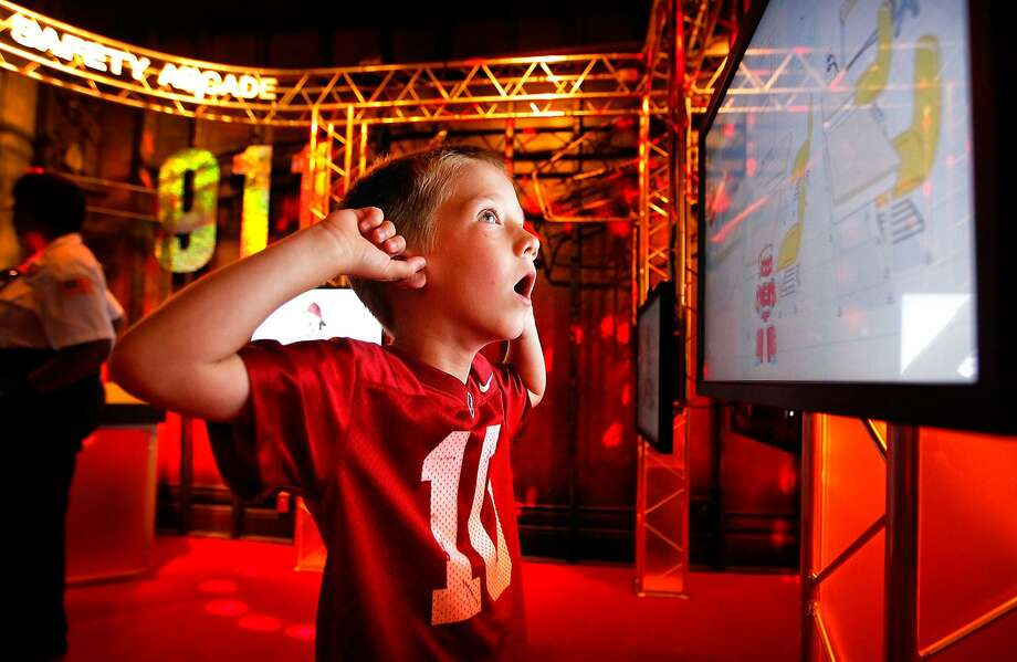 Isaiah Patterson, 6, anticipates the fire alarm sounding during a touch-screen game in the newly renovated Arcade Room exhibit at the Fire Museum of Memphis, Tenn., Monday, June 16, 2014. The game is designed to teach basic lessons of fire safety like stop-drop-and-roll. (AP Photo/The Commercial Appeal, Jim Weber) Photo: Jim Weber, Associated Press
