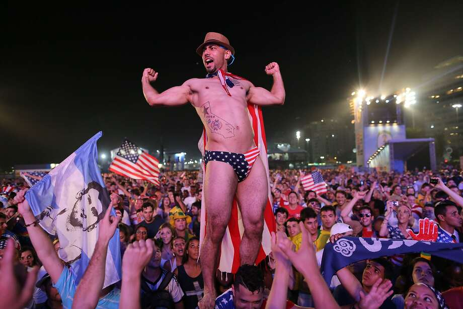 Soccer fans of the U.S. national soccer team cheer minutes before a live broadcast of the soccer World Cup match between USA and Ghana, during a music concert inside the FIFA Fan Fest area on Copacabana beach, Rio de Janeiro, Brazil, Monday, June 16, 2014. (AP Photo/Leo Correa) Photo: Leo Correa, Associated Press