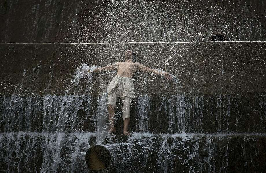 A Pakistani man cools himself in a water stream on the outskirts of Islamabad, Pakistan, on Monday, June 16, 2014, after temperature reached 45 degrees Celsius (113 Fahrenheit). Many cities in Pakistan are facing heat wave conditions with temperatures reaching up to 50 degrees Celsius (122 Fahrenheit) in some places. (AP Photo/B.K. Bangash) Photo: B.K. Bangash, Associated Press