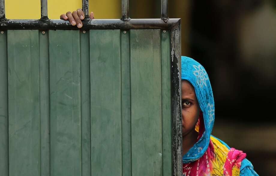A Sri Lankan Muslim woman looks out on the street, in Aluthgama, town, 50 kilometers (31.25 miles) south of Colombo, Sri Lanka, Monday, June 16, 2014. At least three Muslims were killed after a right-wing Buddhist group with alleged state backing clashed with Muslims in southwestern Sri Lanka, a government minister said Monday. Dozens of shops were burned, homes looted and some mosques attacked in the violence Sunday night in the town of Aluthgama, local residents said. (AP Photo/Eranga Jayawardena) Photo: Eranga Jayawardena, Associated Press